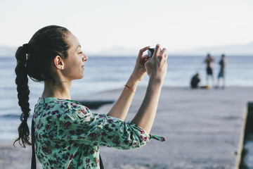 Beautiful woman taking pictures by the sea