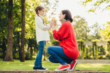 Young mother in warm knitted red sweater plays with her small daughter in park, gives her leaf, enjoy sunny autumn weather. Affectionate mom and little child spend time together outdoor