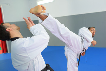 men in white kimono and black belt training karate