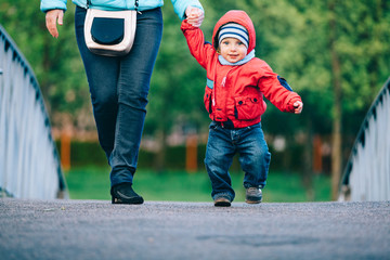 Little boy with mother walking outdoors holding mother's hand