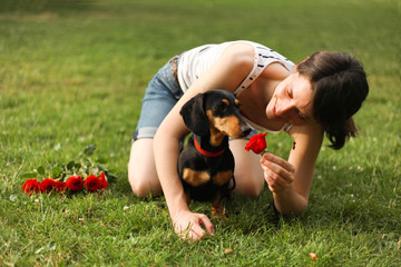 Woman sitting on grass with her small black dog near a bouquet of roses