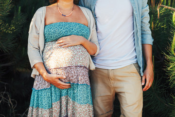 Closeup of a young pregnant couple standing outside.
