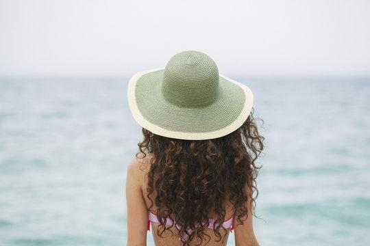 Young girl looking at the horizon at the sea