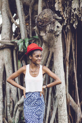 beautiful black woman in front of an anciet tree