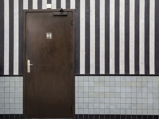 Door to a public bathroom and a striped wall