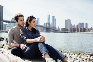 Relaxed couple sitting along the river with Manhattan on the background