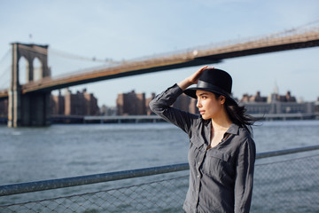 Beautiful girl walking along the East River with the Manhattan Bridge on the background