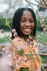 Smiling African American girl standing next to peach tree flowers