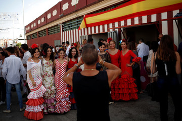 A man takes a photo of women wearing traditional sevillana dresses next to a banner with the colors of the Spanish flag, as they take part in the Fuengirola's fair during Spain's National Day