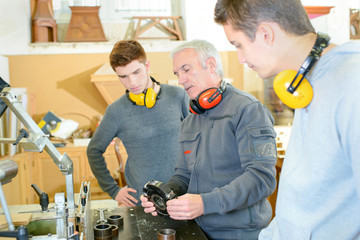 carpenter trainees learning with boss about machinery