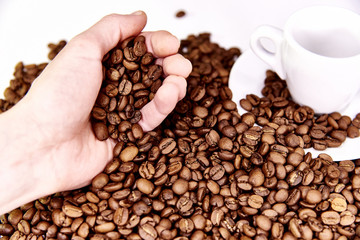 A hand is pouring coffee beans near a white cup