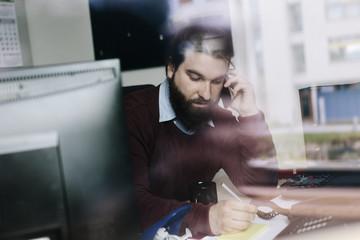 Businessman writing while calling on Telephone
