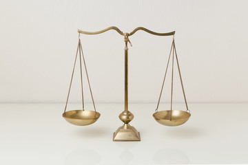 Gold brass balance scale on white glass table. Sign of justice, lawyer