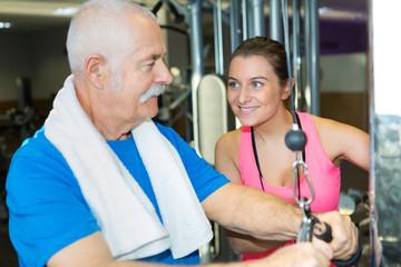 female trainer helping senior man at gym