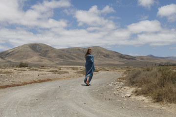 young woman  with blue blanket walking through deserted landscape