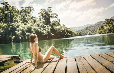 Young woman traveler on wooden pier dock in Cheow Lan Lake at Khao Sok national park - Wanderlust world travel concept with girl tourist wanderer on excursion in Thailand - Warm retro turquoise filter