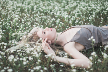 Prretty blond girl laying on the grass