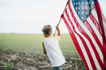 boy running through a field, holding an American flag