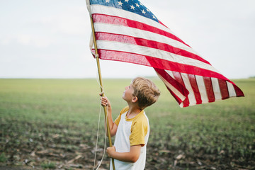 Boy looking at an American flag while standing in a field
