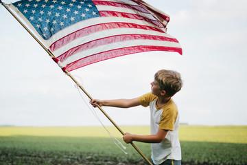 boy waving a large American flag