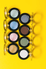 Overhead of eyeshadows palette on a yellow background.