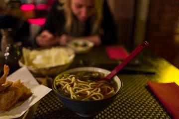 Ramen noodles in Japanese Restaurant with blonde girl