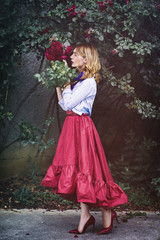 Beautiful young woman in a red skirt smelling roses
