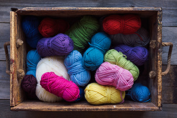 Colourful balls of wool in a wood box