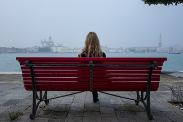 Blonde girl on bench in Venice