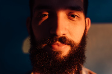 Portrait of bearded man against the blue wall on sunset light