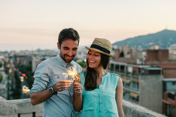 Young couple playing with sparklers standing on a rooftop at sunset.