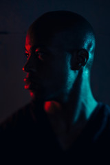 Dark portrait of a black man with red and blue lights