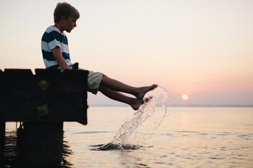 boy splashing his feet in a lake at sunset