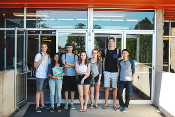 Group of serious high school teens standing in front of school on summer day