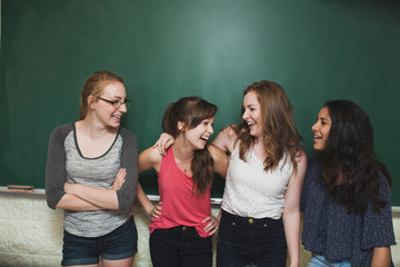 Group high school girls laughing in front of green chalkboard