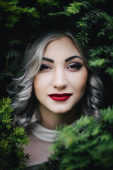 Red lips girl with grey curl hair in green bush