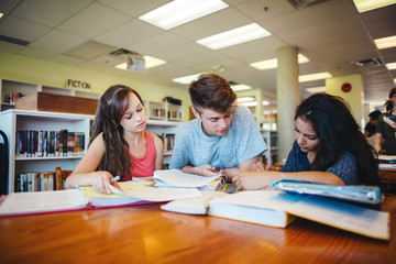 Three high school students studying together in library