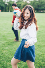 Young Asian Girl Throwing a Rugby Ball