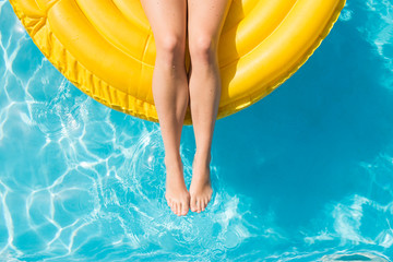 Woman floating on inflatable tube in summer in swimming pool on vacation