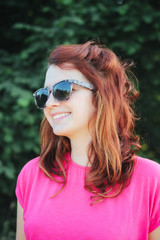 Portrait of a young female redhead model with sunglasses