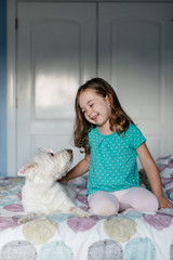 Beautiful young girl petting a small dog on her bed