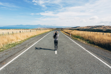 A girl takes a photo from the middle of a highway