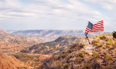 Man Proudly Waving An American Flag On A Canyon Overlook