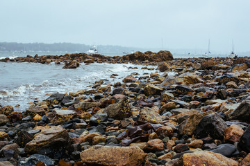 A rocky beach in New England during a rain storm.
