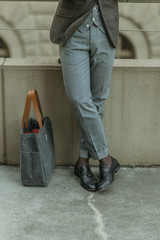 Business man's legs standing next to his work bag