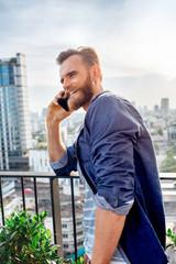 Handsome Bearded Man Makes a Phone Call on a Balcony