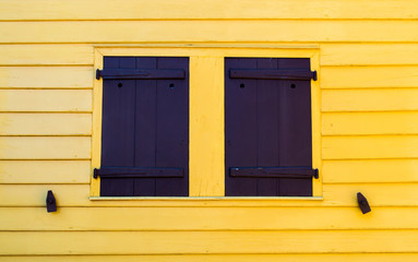 bright yellow wall with black shutters and shutter dogs on a colonial building
