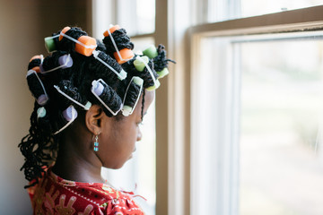 Black girl with curlers in her hair looking out the window