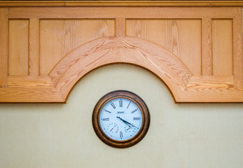 classic wall clock with Roman numerals beneath a carved wooden panel