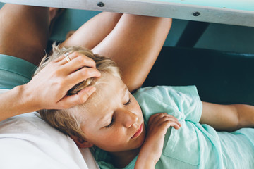 overhead of a child asleep on his mother's lap